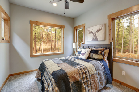 Country style bedroom with wooden bed and beautiful view of the back yard.