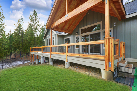 View of a spacious walkout deck with wooden railings of a charming country house.