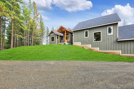 New gray wooden country house exterior with blue sky and green grass.
