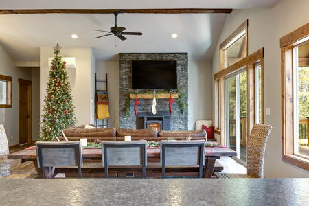 Living room interior with stone fireplace, Christmas decor and deck.