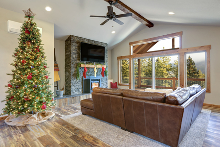 Christmas room interior design. Living space features beamed ceiling, stone fireplace and decorated Christmas tree. Stockfoto - 114014720