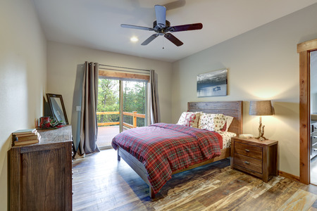 Restful country master bedroom furnished with wooden bed, nightstand and dresser