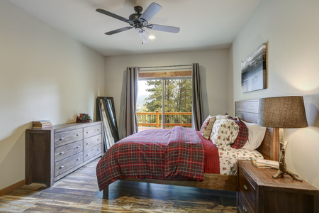 Restful country bedroom furnished with wooden master bed, dark gray dresser and view of spacious deck