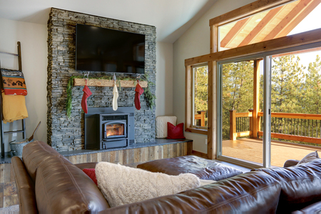 Living room interior with stone fireplace, Christmas decor and deck. Stockfoto - 114014731