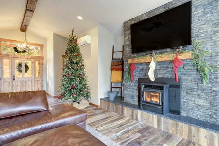 Nicely decorated home interior for Christmas. Living area boasts grey stone fireplace with stockings, rustic wood floor and high vaulted ceiling.