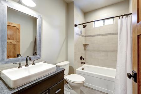 Interno del bagno bianco e fresco con un lavandino rettangolare e bordo doccia in piastrelle della metropolitana avorio.