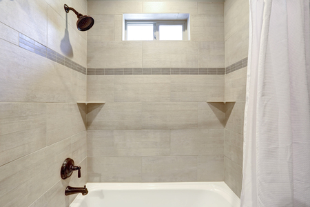 White and fresh bathroom interior with ivory subway tile shower surround .
