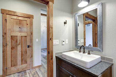 White and fresh bathroom interior with a rectangular vessel sink and dark gray countertop.