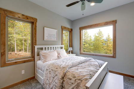 Small yet cozy bedroom interior, white bed with headboard, pale pink bedding and bench Stockfoto