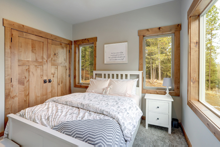 Small yet cozy bedroom interior features wooden closet doors, white bed with headboard, pale pink and gray bedding Stockfoto - 114014822