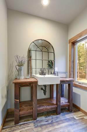 Fantastic bathroom boasts a country style washstand adorned with iron cage mirror Zdjęcie Seryjne - 114014824