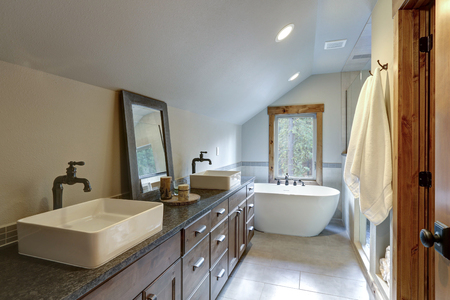 Wonderfully designed bathroom in a country house boasts dual washstand with dark granite countertop and rectangular vessel sinks.