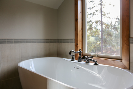 View of bathroom design with a white sleek freestanding tub under a window paired with an oil rubbed bronze faucet.