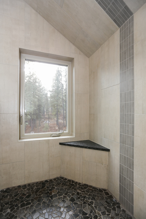 Country bathroom interior with vertical ivory subway tile shower surround and stone floor. Stockfoto