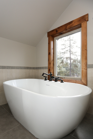 View of bathroom design with a white sleek freestanding tub under a window paired with an oil rubbed bronze faucet. Zdjęcie Seryjne - 114014829