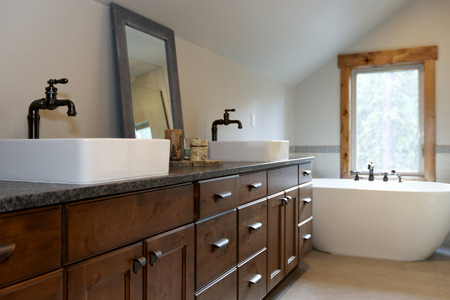 Wonderfully designed bathroom in a country house boasts dual washstand with dark granite countertop and rectangular vessel sinks. Stockfoto - 114014830