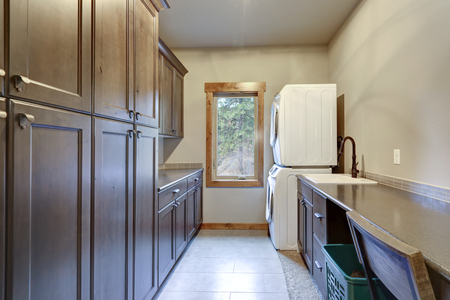 Laundry room with a stacked white front loading washer and dryer, floor to ceiling dark shaker cabinets. Zdjęcie Seryjne - 114014831