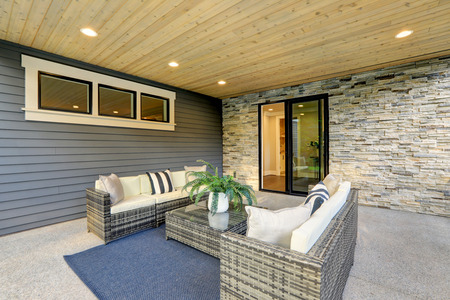 Luxury modern house exterior with covered patio boasting stone fireplace and cozy rattan furniture. Stockfoto - 118547116