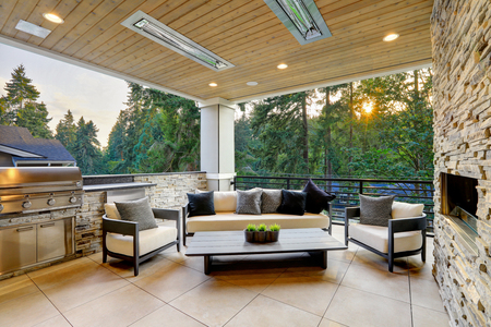 Luxury modern house exterior with covered patio boasting stone fireplace and cozy rattan furniture. Stockfoto