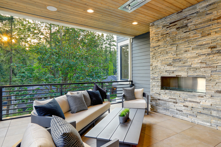 Luxury modern house exterior with covered patio boasting stone fireplace and cozy rattan furniture. Фото со стока