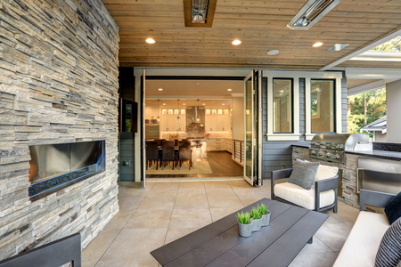 Luxury modern house exterior with covered patio boasting stone fireplace and cozy furniture. Zdjęcie Seryjne - 118547122