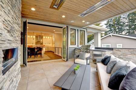 Luxury modern house exterior with covered patio boasting stone fireplace and cozy furniture.