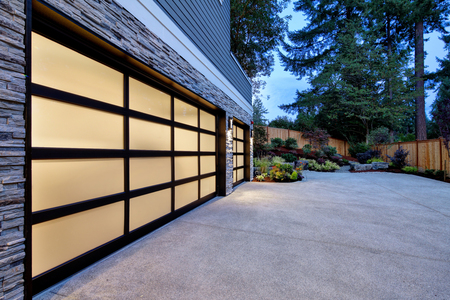Modern house exterior with two car garage, spacious driveway at twilight Stockfoto - 118547152