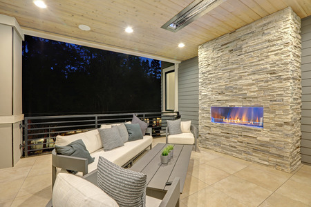 Luxury covered patio with stone fireplace and cozy interior