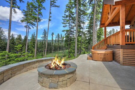 New Mountain vacation Cedar brown home exterior with great back porch with hot tub and fire pit.