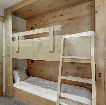 Smart home with wooden bunk beds in a hallway for adults or kids and open door to bathroom.