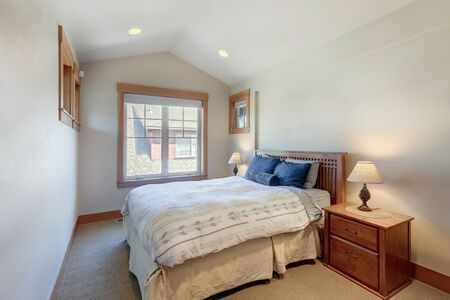 Guest bedroom with wooden bed and great windows with beige carpet. white and blue sheets.