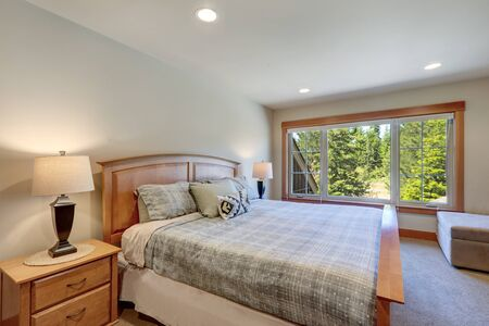 Guest bedroom with wooden bed and great windows with beige carpet. white and blue sheets and huge windows.