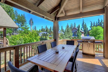 Beautiful covered deck with large luxury dining room table with grill and railings. Lots of pine trees. Banque d'images