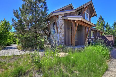 Grey wooden rustic house front exterior  with pine trees and flowers and grass during summer