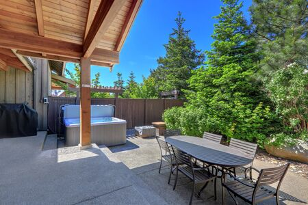 Small and green back yard space with fire and hot tub and large dining room table and grill