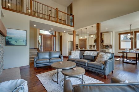 An absolute beautiful luxury living room with huge vaulted ceiling, fire place, harwood floor, amazing furniture, and lots of windows and doors. Solid wood rustic modern dining room table.