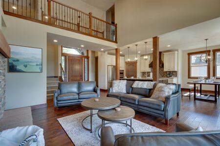 Un salon de luxe absolu avec un immense plafond voûté, une cheminée, du parquet, des meubles incroyables et de nombreuses fenêtres et portes. Table de salle à manger moderne rustique en bois massif.