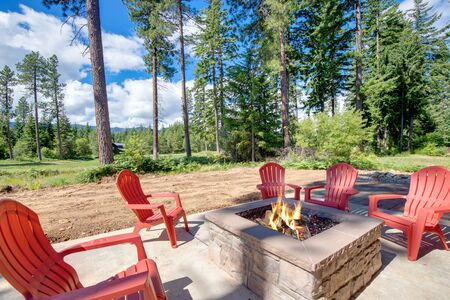 Huge open to nature Back yard with fire pit , amazing patio and red chairs near newly bild luxury real estate home with forest biew and green grass.
