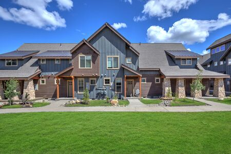 Newly build modern and rustic home from exterior in natural brown and grey colors with walkways, green grass and natural stone. Blue sky and sunny day. American new archtecture. Foto de archivo
