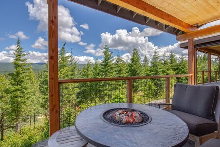 Amazing balcony patio with fire pit and forest and mountains view. Dream come true home exterior. New American architecture. Comfortable and beautiful home details.