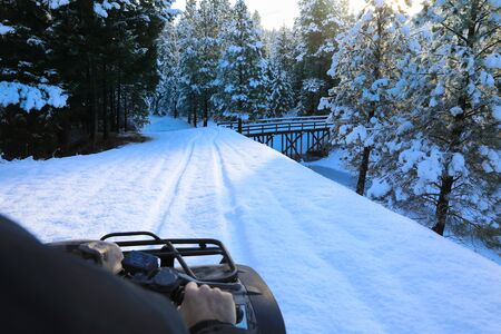 Man riding snowmobile or fourwheeler on the country side trail near water canal. Banque d'images
