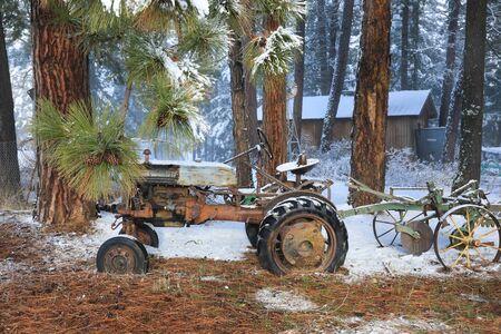 Vieux paysage de campagne américaine d'hiver avec des maisons rustiques, des voitures et des clôtures couvertes de neige.