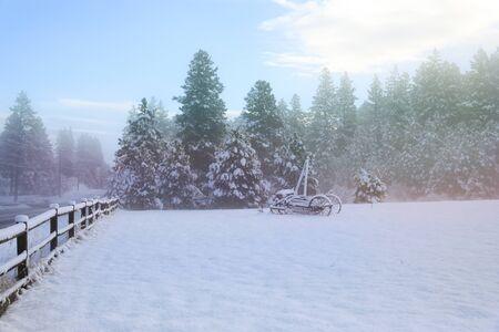 Vieux paysage de campagne américaine d'hiver avec des maisons rustiques, des voitures et des clôtures couvertes de neige. Banque d'images