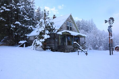 Winter old American Country side landscape with rustic houses, cars and fences covered in snow. Standard-Bild