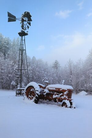 Winter old American Country side landscape with rustic houses, cars and fences covered in snow.