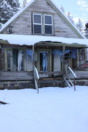 Winter old American Country side landscape with rustic houses, cars and fences covered in snow. Banque d'images