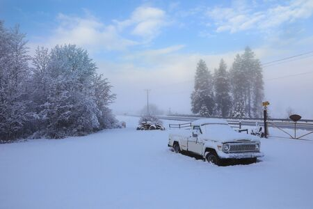 Winter old American Country side landscape with rustic houses, cars and fences covered in snow. Banque d'images - 142944690