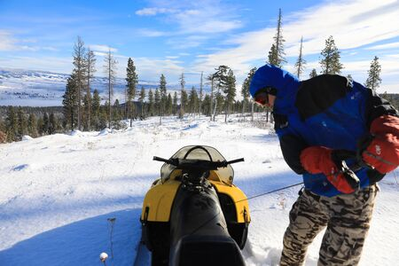 Man riding snowmobile in the mountains with pine trees and houses. Banque d'images - 142944859