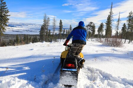 Man riding snowmobile in the mountains with pine trees and houses. Banque d'images - 142945083