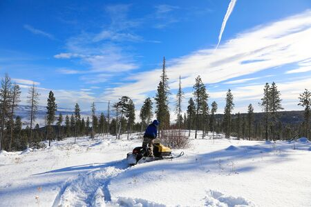 Man riding snowmobile in the mountains with pine trees and houses. Banque d'images